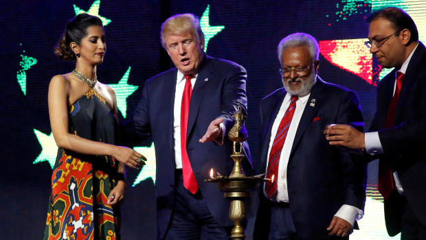 Republican presidential nominee Donald Trump enlists the help of Republican Hindu Coalition Chairman Shalli Kumar to light a ceremonial diya lamp in Edison, New Jersey